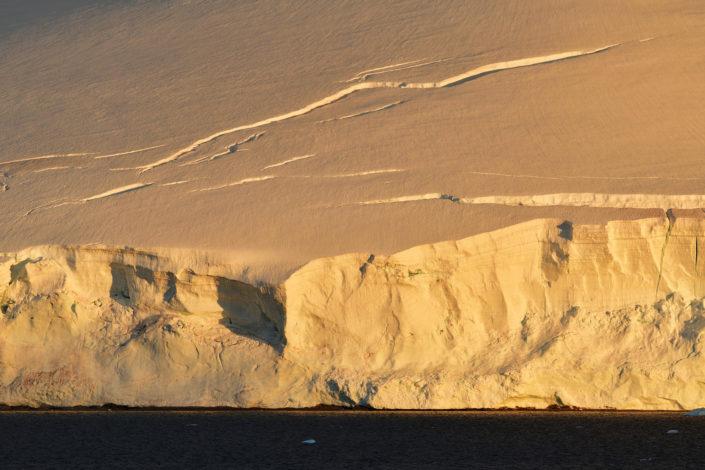 The sun casts an orange glow on the ice of Rongé Island. © YvesAdams